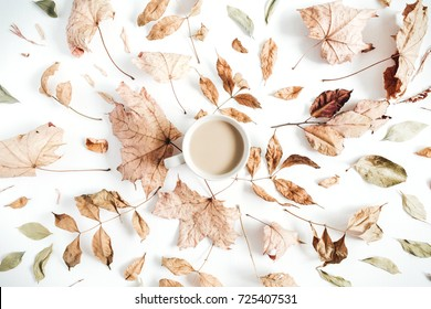 Coffee with milk and dry autumn leaves on white background. Flat lay, top view fall concept.