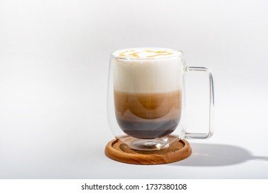 Coffee with Milk froth and caramel in double layer grass on woodplate
