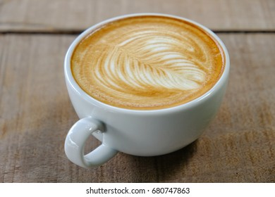 coffee with milk on wood table, beautiful latte art