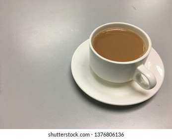 Coffee with milk in a white cup on the table.