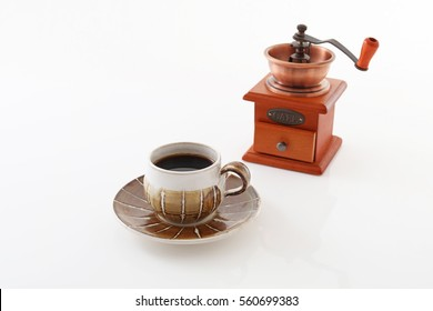 Coffee mill and a cup of coffee on the table