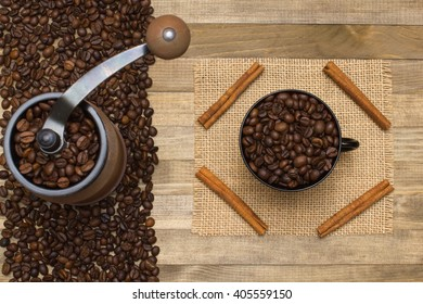 coffee mill and strip coffee beans on wooden background