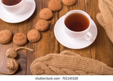 Coffee, mittens and oat cookie on wood
