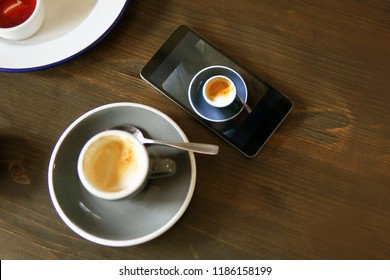 Coffee and mobile phone with a photo of coffee cup. Picture in picture concept