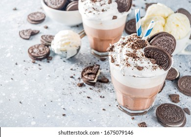 Coffee mocha milkshake with cookies and cream. Ice cream and chocolate cookies sweet latte cocktail. On gray concrete table, with spoon and cup of vanilla ice cream. Copy space