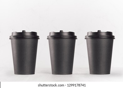 Coffee mockup - set of three blank black paper cups with cap on white wood table, coffee shop interior. Modern elegant concept for branding identity, advertising, design.