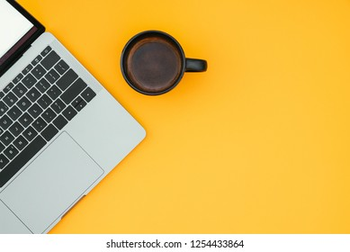 Сup of coffee and a modern notebook are isolated on a yellow background, a place for text, a workplace on a colored background. Copyspace