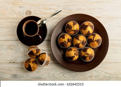 Coffee with muffins on a light wooden background. Selective focus.