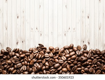 A coffee mug of coffee beans on wood background