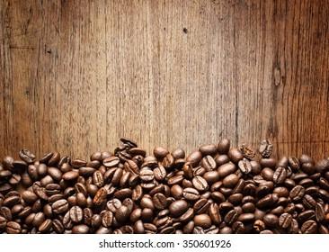 A coffee mug of coffee beans on wood background