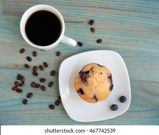 coffee in a mug with a blue berry muffin on a white plate with coffee beans on a green wooden background