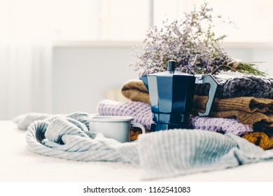 Coffee mug and blue geyser coffee pot on a white coverlet, a stack of knitted clothes and a scarf