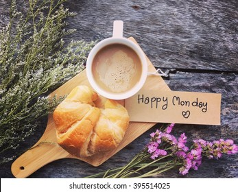 Coffee mug with croissant and flowers and notes happy Monday on blue rustic table.