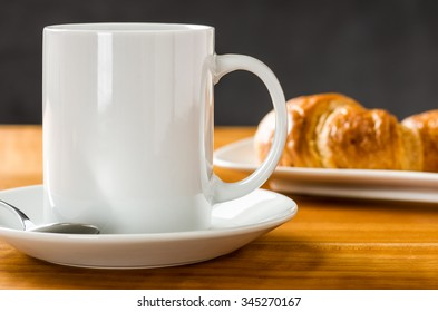 A coffee mug with croissants on a dark background