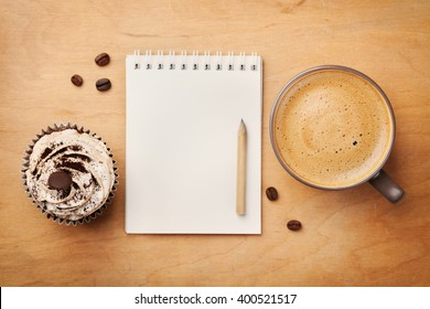 Coffee mug with cupcake, notebook and pencil on rustic table from above, cozy and sweet breakfast, good morning or have a nice day concept