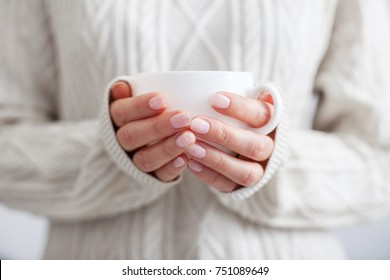 Coffee mug in female hands. Woman drinking hot coffee