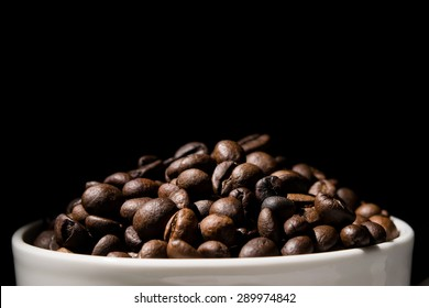 Coffee mug filled with coffee beans over black background