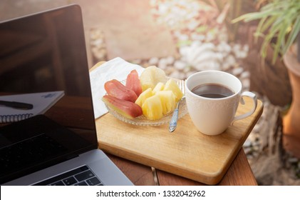 Coffee mug with fresh fruit and laptop on wooden table in the garden.