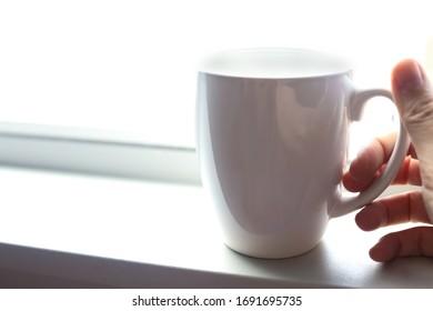 Coffee mug in hand on a bright white windowsill