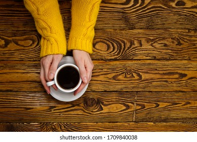 coffee mug in hand on old wooden table top view with copy space. woman in cozy yellow home sweater holding a mug of coffee while enjoying a drink