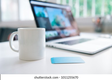 Kaffeemaschine und Laptop im Tischbereich mit Visitenkarte