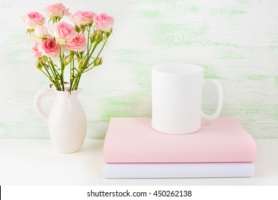 Coffee mug mockup with books and pink roses. Coffee cup mock-up for brand promotion.  Empty mug mockup for design presentation.