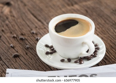 Coffee mug with newspaper on wooden table