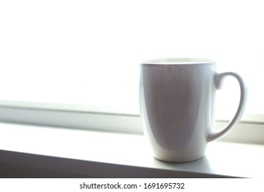Coffee mug on a bright white windowsill