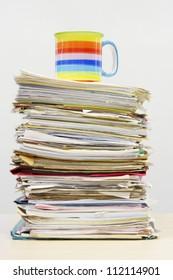 Coffee mug on stack of file folders