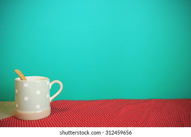 Coffee mug on tablecloth front mint green background. Vintage effect.