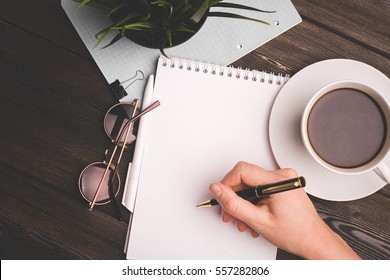 coffee mug, pen, notebook on the table