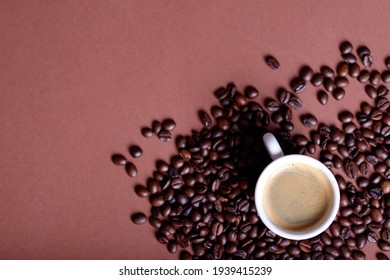 Coffee mug with roasted beans on stone background. Top view with copy space