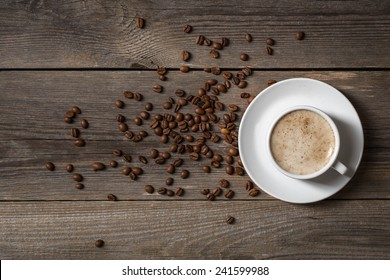 Coffee mug with roasted coffee beans on wooden table. View from top