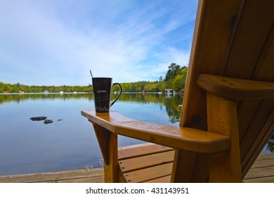A coffee mug sitting on a Muskoka chair on a dock. Lake and cottages in the background - horizontal orientation. Perfect for cottage related material