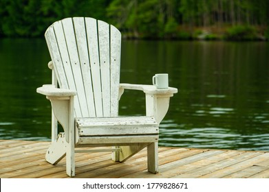 A coffee mug sitting on a white Adirondack chair on a wooden dock near the water.