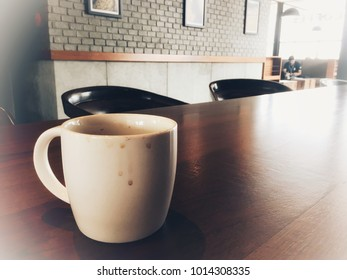 Coffee mug with stain on wooden table, vintage concept