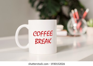Coffee mug with text - COFFEE BREAK in workplace background.