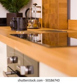 Coffee mugs and cafetiere on worktop in modern designer kitchen
