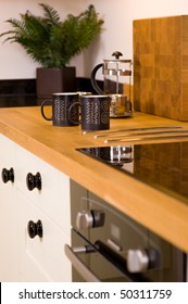 Coffee mugs and cafetiere on worktop in modern designer kitchen