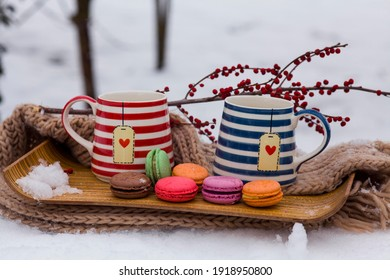 Coffee mugs with macarons with snow view