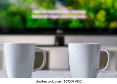 Coffee mugs with a television with a nature documentary and subtitles in background