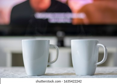 Coffee mugs with a television screen with a movie and subtitles in background.