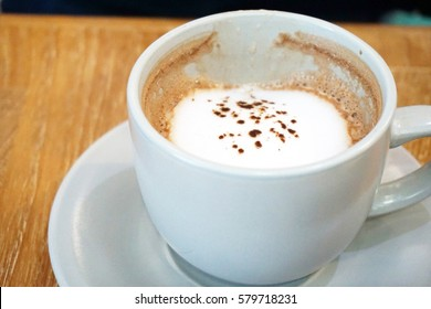 Coffee on froth at wooden table.