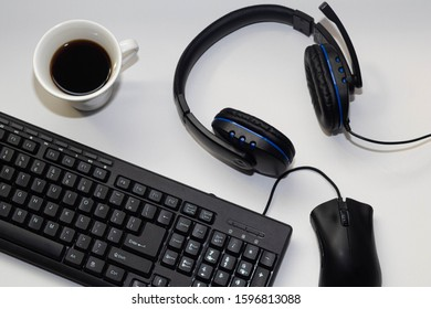Coffee on a wooden table with a white background with a computer keyboard a mouse and a mobile phone on the table.