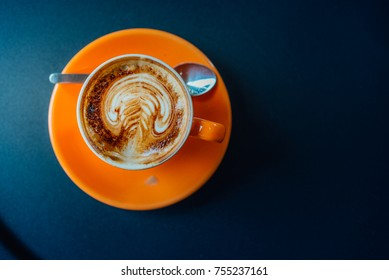 coffee in orang cup on black table top