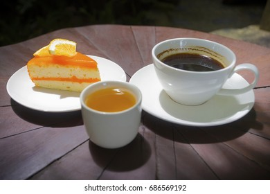 Coffee with orange cake on wood background