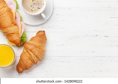 Coffee, orange juice and croissant sandwich on wooden table. French breakfast. Top view flat lay with copy space for your text
