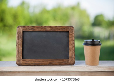 coffee paper cup with chalk board, on wood table, summer day background.