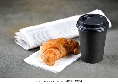 Coffee in a paper cup, croissant and newspaper. Concept of morning coffee and fresh news. Dark background. Close-up.