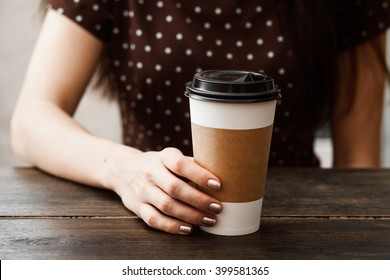 Coffee paper cup in the girl hands, kraft style